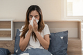 Asian woman feeling unwell and sneezing on the bed - PhotoDune Item for Sale