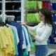 Pretty Girl Chooses Clothes in Store, Woman Choose T-shirt - VideoHive Item for Sale