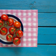 Red tomatoes lie on a plate on a blue wooden background, top vie - PhotoDune Item for Sale
