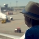 One Boy Looks at Airplane Runway in a Airport Waiting for a Trip - VideoHive Item for Sale