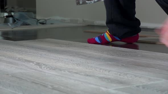 Handyman Hands Laying Down Laminate Wood Flooring Boards By Sauletas