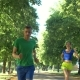 Cheerful Female Runner Overtake Man on Park Trail - VideoHive Item for Sale