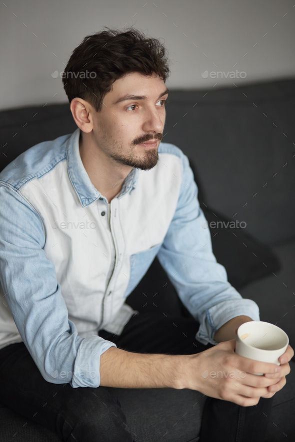 Freelancer resting with a cup of coffee on a couch while thinkin - Stock Photo - Images