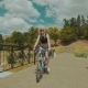 Beautiful Young Woman Smiling While Riding Her Bicycle on Sunny Summer Day - VideoHive Item for Sale