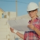 A Female Engineer Is Studying a Drawing. It Stands on the Construction Site of a Small Cottage - VideoHive Item for Sale