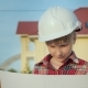 A Small Architect in a White Helmet Is Carefully Studying the Drawing on the Construction Site - VideoHive Item for Sale