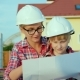 A Woman in a Helmet with a Child Looks at the Drawing of the House - VideoHive Item for Sale