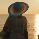 A Young Woman in Beach Clothes and a Wide-brimmed Hat Is Enjoying the Sunrise on the Seashore - VideoHive Item for Sale