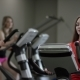 Cute Girl in Red Shirt Vigorously Work on Exercise Bike and Trainer Come Greed Her in the New Gym - VideoHive Item for Sale