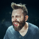 Young handsome man with beard sneezing, studio portrait - PhotoDune Item for Sale
