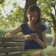 Smiling Pretty Woman Texting on Cellphone in Park - VideoHive Item for Sale
