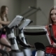 Lovely Girl in Red Shirt Vigorously Works on Exercise Bike and Talks with Her Phone with Headphone - VideoHive Item for Sale