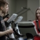 Lovely Girl in Red Shirt Vigorously Works on Exercise Bike and Guy Comes To Take Her Number in the - VideoHive Item for Sale