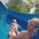 A Young Family of Three People Is Having Fun in the Water Park, Going Down Into the Water Slide One - VideoHive Item for Sale