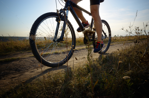 Male cyclist driving by rural dirt road outdoors. Low angle view - Stock Photo - Images