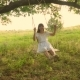 Teenage Girl with Long Hair in a White Dress Laughs Rolling on a Swing Under a Summer Oak Tree - VideoHive Item for Sale