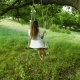 Female with Long Hair in a White Dress Swinging on a Swing Under a Summer Oak Tree in the Warm - VideoHive Item for Sale