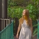 Steadicam Shot of a Young Woman Walking on the Hanging Suspension Bridge in the Eco Park - VideoHive Item for Sale