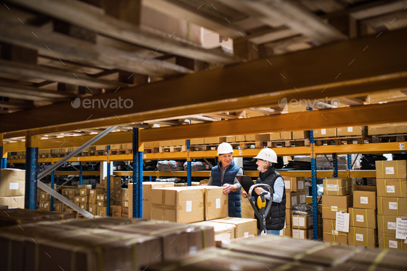 Senior woman and man managers or supervisors working in a warehouse. - Stock Photo - Images