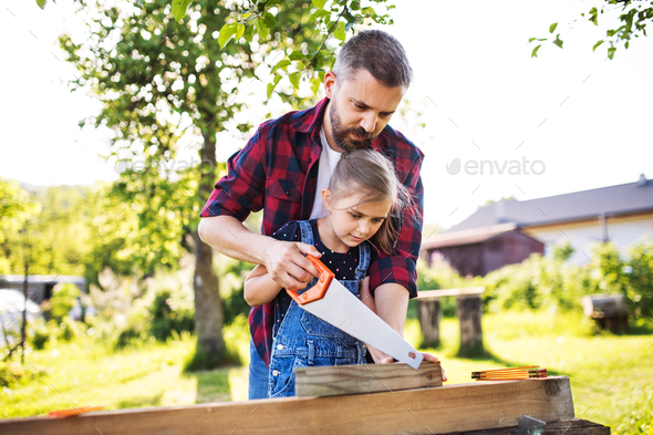 Father and a small daughter with a saw outside, making wooden birdhouse. - Stock Photo - Images