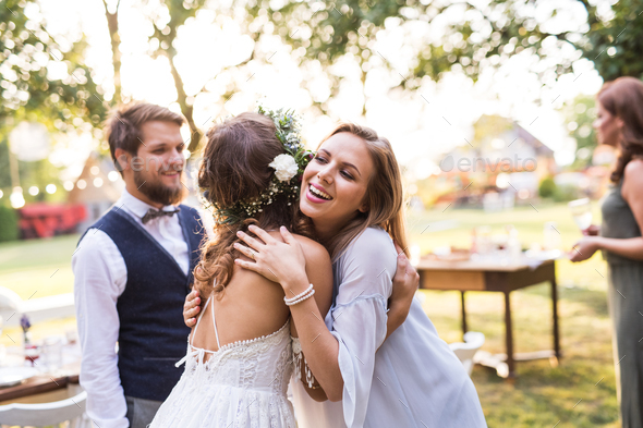 Young girl congratulating bride and groom at wedding reception in the backyard. - Stock Photo - Images