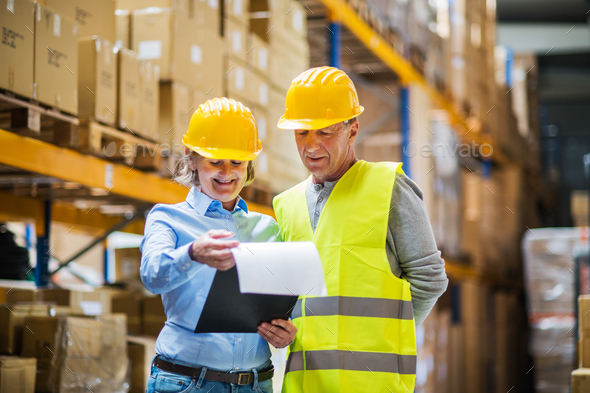 Senior woman manager and man worker working in a warehouse. - Stock Photo - Images