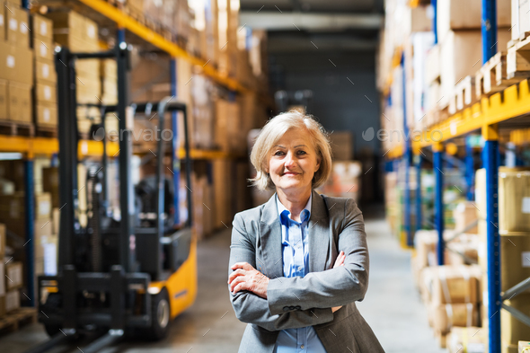 Senior woman warehouse manager or supervisor , arms crossed. - Stock Photo - Images