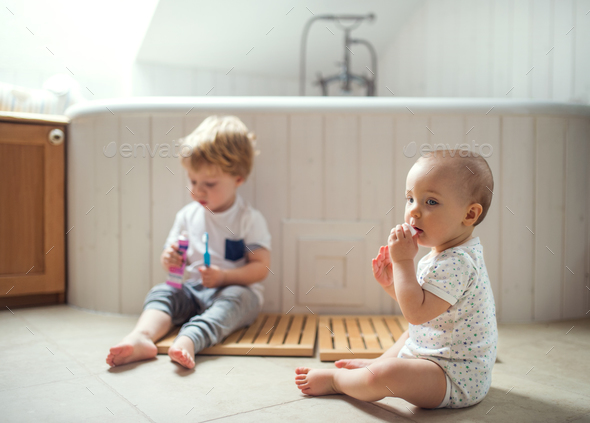 Two toddler children brushing teeth in the bathroom at home. - Stock Photo - Images