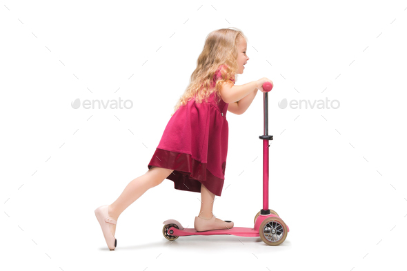 Smiling cute toddler girl three years riding a scooter over white background - Stock Photo - Images