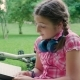 Cute Yung Girl Smiles While Reading a Book in the Park - VideoHive Item for Sale