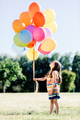 Little girl holding a bunch of colorful balloons in the park. - PhotoDune Item for Sale