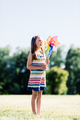 Little girl blowing upon a pinwheel in the park. - PhotoDune Item for Sale