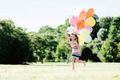 Young girl running on the grass field with balloons. - PhotoDune Item for Sale