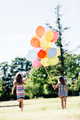 Two little girls holding a bunch of balloons together. - PhotoDune Item for Sale