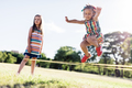 Little girl in a colorful dress jumping through the elastic. - PhotoDune Item for Sale
