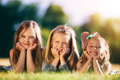 Three smiling little girls laying on the grass in the park. - PhotoDune Item for Sale