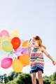 Happy girl running with a bunch of colorful balloons. - PhotoDune Item for Sale
