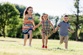 Two little girls and a boy running on the grass field. - PhotoDune Item for Sale