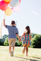 Young boy and a girl running with a bunch of colorful balloons. - PhotoDune Item for Sale