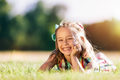 Little smiling girl laying on the grass field in the park. - PhotoDune Item for Sale