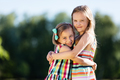 Two little girls hugging each other in the park. - PhotoDune Item for Sale