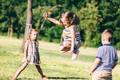 Little girl jumping through the elastic, playing with other children. - PhotoDune Item for Sale