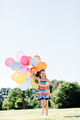 Young girl in a dress running with a bunch of balloons. - PhotoDune Item for Sale