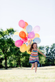 Happy girl in running with a bunch of balloons - PhotoDune Item for Sale