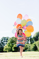 Happy little girl running with a bunch of colorful balloons - PhotoDune Item for Sale