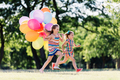 Two little happy girls running with a bunch of colorful balloons. - PhotoDune Item for Sale