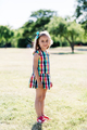 A young happy girl in colorful checkered dress standing in the park, - PhotoDune Item for Sale