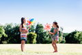 Two little girls blowing upon colorful pinwheels. - PhotoDune Item for Sale
