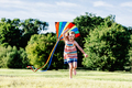 Happy girl running on the grass field with a colorful kite. - PhotoDune Item for Sale