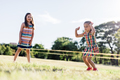 Two girls playing Chinese jumping rope in the park. - PhotoDune Item for Sale